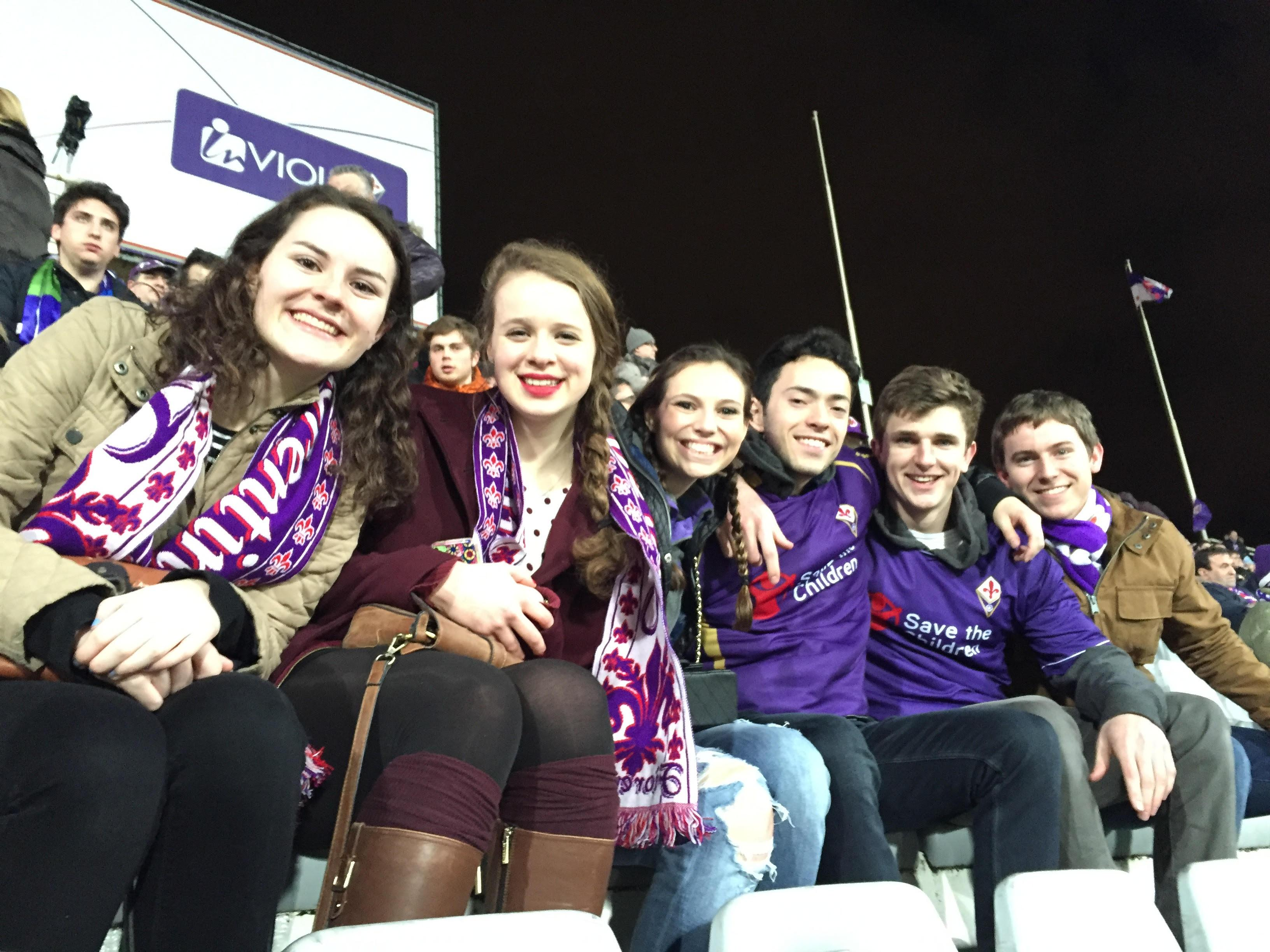 Students wearing AC Fiorentina scarves at a soccer game.