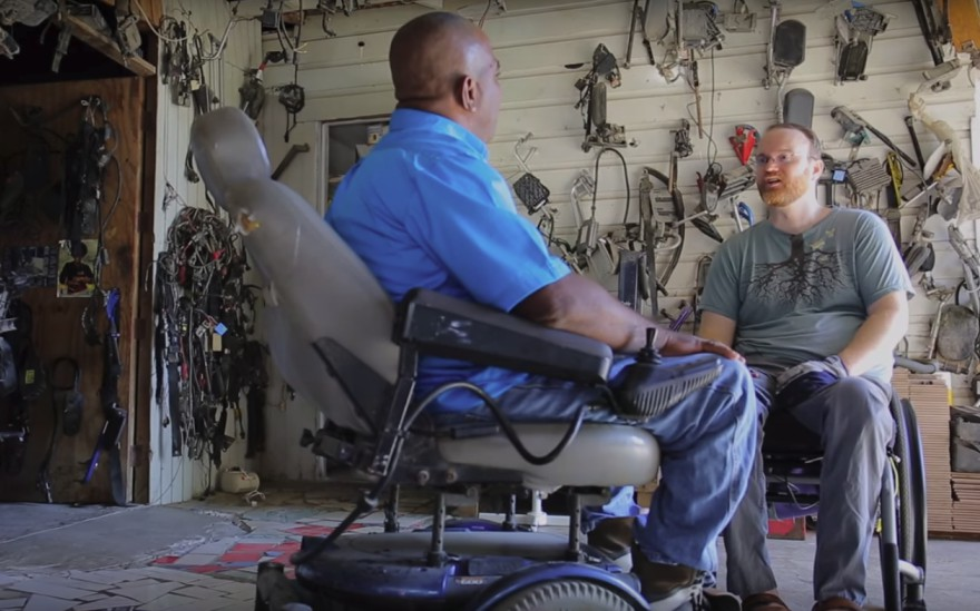 James Sullivan speaks with another individual while documenting disability in the developing world.